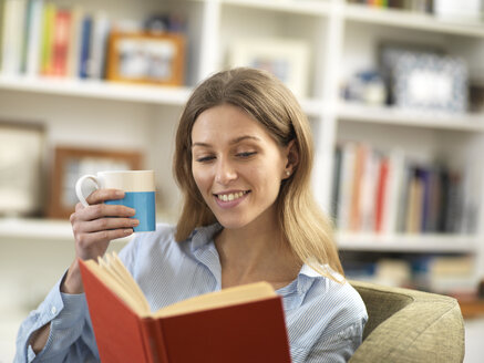 Smiling young woman with a hot drink relaxing at home reading a book - ABRF00283