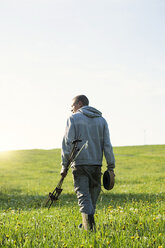 Farmer walking on his land through a meadow with dandelions - SBOF01693