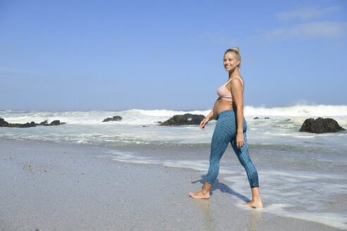 Portrait of happy pregnant woman on the beach wading in the sea - ECPF00357