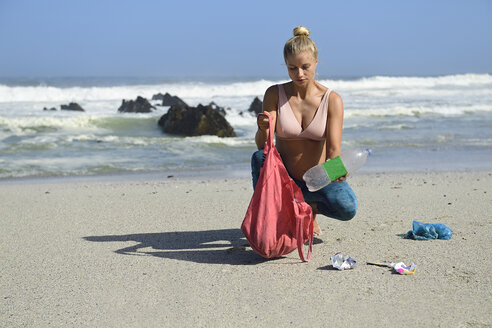 Pregnant woman cleaning the beach from plastic waste - ECPF00360