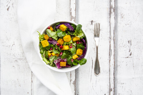 Mixed salad with roasted tofu, red cabbage, pomegranate seeds and curcuma in bowl on white wood - LVF07737