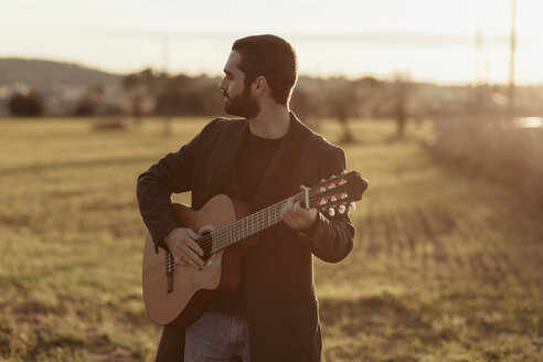 Male musician with beard playing the guitar in the countryside - LOTF00058