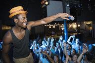 DJ with microphone above cheering nightclub crowd - HEROF14900