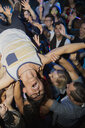 Enthusiastic man crowdsurfing at concert - HEROF14906