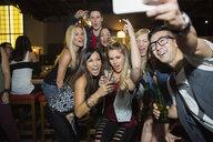 Enthusiastic friends taking selfie at bar - HEROF14921