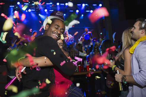 Confetti falling hugging couple enjoying New Year celebration - HEROF14948