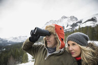 Couple with binoculars bird watching below snowy mountain - HEROF14987