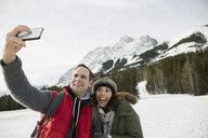Couple taking selfie below snowy mountains - HEROF14993