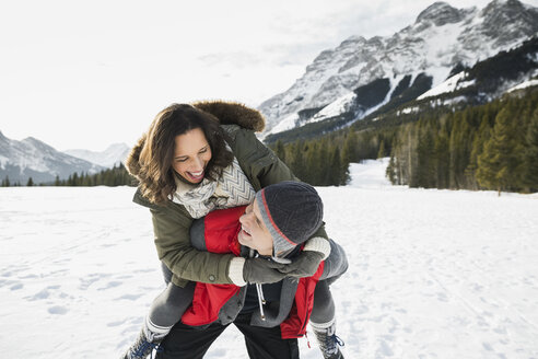 Couple piggybacking in snowy field below mountains - HEROF15002