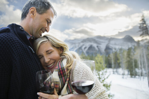 Couple with wine hugging with mountains in background - HEROF15041