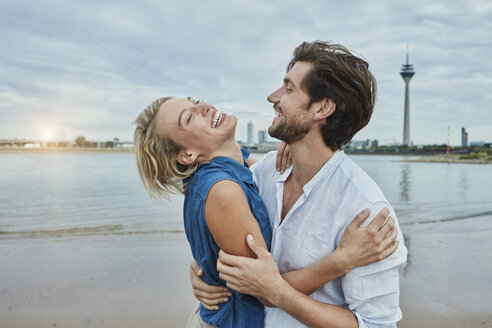 Germany, Duesseldorf, happy young couple at Rhine riverbank - RORF01668