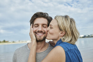 Happy young couple kissing on the beach - RORF01680