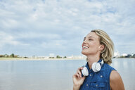 Germany, Duesseldorf, happy young woman with headphones at Rhine riverbank - RORF01683