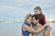 Germany, Duesseldorf, happy family with daughter hugging at Rhine riverbank - RORF01701