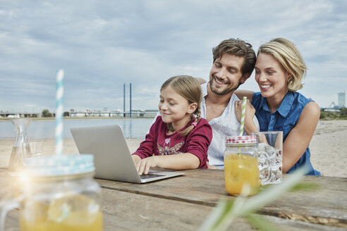 Germany, Duesseldorf, happy family with daughter using laptop on wooden table at Rhine riverbank - RORF01710