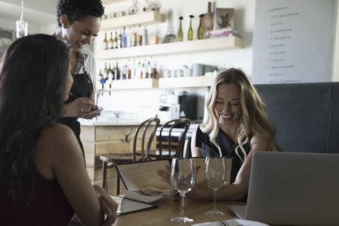 Businesswomen ordering from waitress at cafe - HEROF15081