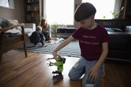 Boy playing with robot toy on living room floor - HEROF15114
