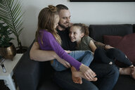 Affectionate father and daughters bonding, cuddling on living room sofa - HEROF15126