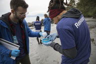 Eco-friendly male scientists gathering micro plastic specimens on beach - HEROF15156