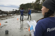 Eco-friendly female scientist with clipboard on beach - HEROF15162