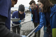 Eco-friendly scientists with screen examining micro plastics on beach - HEROF15165