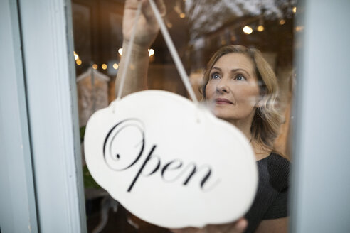Bridal boutique owner hanging open sign in window - HEROF15189