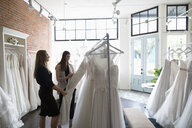 Bride and friend shopping for wedding dresses in bridal boutique - HEROF15195