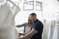 Bride and groom shopping for wedding dresses in bridal boutique - HEROF15201