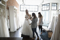 Bride and friends at wedding dress fitting in bridal boutique - HEROF15204