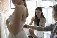 Bride and friends at wedding dress fitting in bridal boutique - HEROF15207