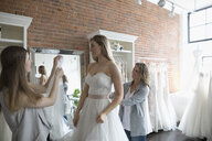 Bride and friends at wedding dress fitting in bridal boutique - HEROF15210