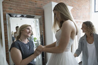 Bride and affectionate mother at wedding dress fitting in bridal boutique - HEROF15213