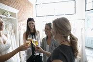 Bride, mother and friends toasting champagne at wedding dress fitting at bridal boutique - HEROF15216