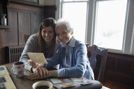 Affectionate senior mother and daughter looking at photo albums - HEROF15231