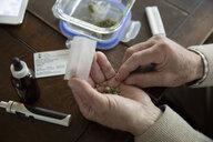 Close up senior man rolling medicinal marijuana joint - HEROF15234
