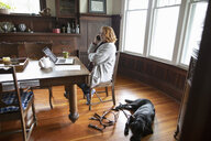 Black seeing eye dog laying on floor next to owner talking on phone at dining table - HEROF15240