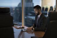 Dedicated businessman working late at laptop in boardroom - HEROF15249