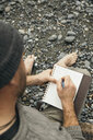 Barefoot man writing in journal on rugged beach - HEROF15285