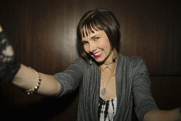 Confident, happy female millennial taking selfie in nightclub - HEROF15291