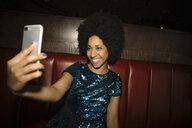 Confident female millennial taking selfie with smart phone in nightclub - HEROF15294
