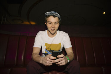 Cool male millennial using smart phone in nightclub - HEROF15300