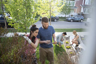 Couples with digital tablet gardening, doing yard work in front yard - HEROF15336