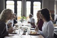 Women friends eating sushi, dining at restaurant - HEROF15414