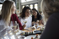 Women friends drinking wine and eating sushi at restaurant - HEROF15420