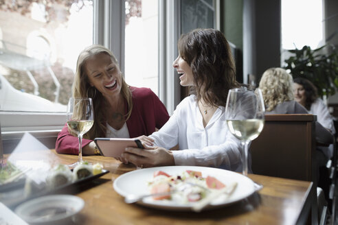 Women friends with smart phone drinking wine and eating sushi, dining at restaurant - HEROF15423