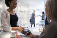 Young woman with smart phone paying with contactless payment in boutique - HEROF15438
