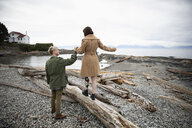 Young man holding hands with amputee girlfriend walking on beach driftwood - HEROF15480