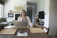 Woman working from home, using laptop in dining room - HEROF15513