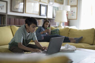 Tween boy using laptop on sofa and sister texting in background - HEROF15519