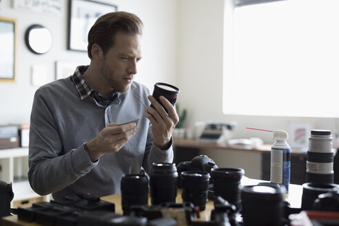 Focused male photographer cleaning camera lenses - HEROF15543